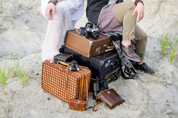 .Boho hippie wedding couple sitting on vintage suitcases, near old retro cameras and camera cases..
