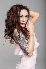 Beautiful funny woman with a haircut with a tattoo on her arm in a pink evening dress on a gray background