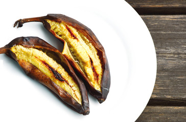Cavendish Bananas grilled on white dish with wooden background