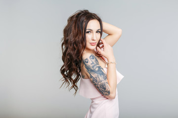 Beautiful young woman with stylish tattoo on hand in pink dress on gray background