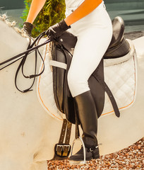 White horse, advanced dressage test on equestrian competition. Professional female horse rider, equine theme. Saddle, bridle, boots and other details.