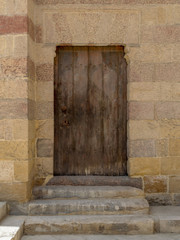 Grunge wooden aged door on exterior stone bricks wall of Amir Aqsunqur Mosque (Blue Mosque), Medieval Cairo, Egypt