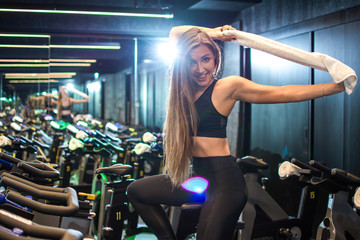 Attractive young girl with towel exercising on stationary bike at gym.