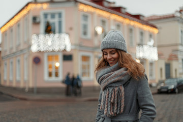 Beautiful young happy girl in stylish fashionable winter knitted clothes with a vintage hat with scarf walking outdoors in the city