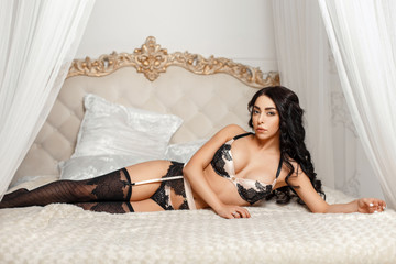Beautiful young girl in sexy lingerie lying on the bed in the bedroom