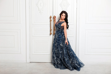 Pretty young stylish woman in a fashion evening dress near a luxury vintage wall