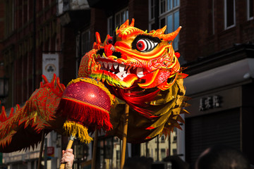 The orange coloured dragon illuminated by the low sunlight during the traditional dance at Chinese New Year in Liverpool.