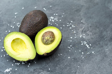 Fresh avocado on black old wooden table.