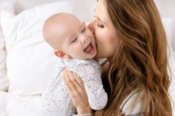 Happy mother kissing her adorable baby son. Happy family. Mother and newborn child playing in nursery portrait.