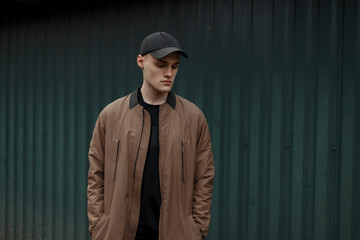 Handsome model man in a fashion vintage coat and a stylish cap near a metal green wall