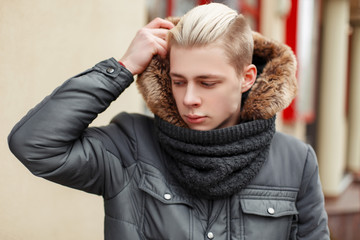 Stylish handsome man with a hairdo in a trendy warm winter jacket with fur on the street