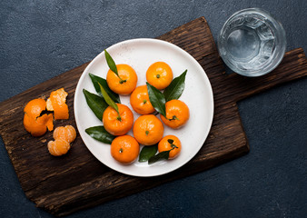 Tangerines with leaves on the plate