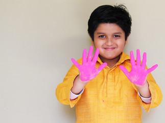 Cute Indian boy celebrating Holi with powder color gulaal