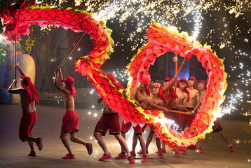 Folk artists perform a fire dragon dance under a shower of sparks from molten iron in Beijing