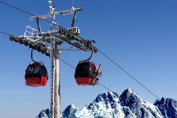 Gondola cabin lift in the ski resort over the high mountains on the blue sky background in sunny day with copy space.