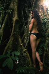 Young sexy woman looking at the big tree jungles. Ecotourism