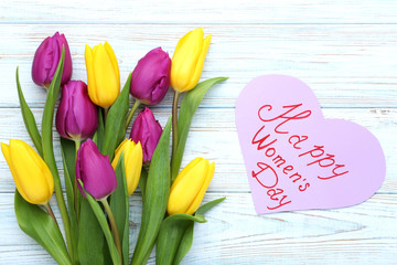 Bouquet of tulips and paper with inscription Happy Women Day