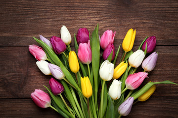 Bouquet of tulips on brown wooden table
