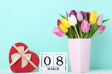Bouquet of tulips with gift box and calendar cubes on wooden table
