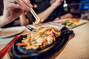 Close up view of woman holding meat in chopsticks while eating Asian food in the restaurant with friends.