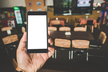 Hand holding black mobile smart phone with blank black screen in coffee shop cafe. technology and lifestyle concept.