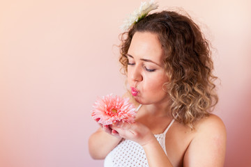 Beautiful curly woman holding pink flower on color background at home. Hello Spring concept.
