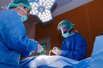 group of Doctor and Assistant surgeons work for rescue patient in operation room at hospital, emergency case, surgery, medical technology, health care cancer and disease treatment concept