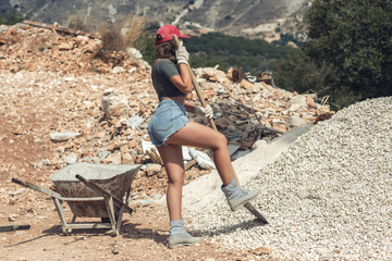 Beautiful woman in the shorts and in the red peaked cap with a wheelbarrow for cement and the shovel digging on stone. Concept of Construction and Mining Industry