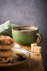Cup of coffee with chocolate chip cookies on green plate on old wooden table. Selective focus.
