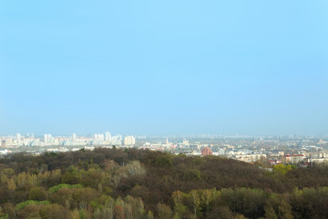 roof view of city along the forest against blue sky.