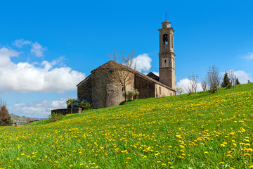 Medieval church on spring field in Italy.