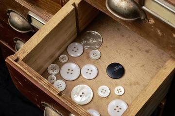 Eine offene schublade in der einige Knöpfe liegen. Ein Knopf ist abgegrenzt von den anderen weil er anders ist. Konzebt beispiel für die ausgrenzung von Ausländern in der Geselschaft