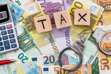 handcuffs and wooden cubes tax text on euro bills