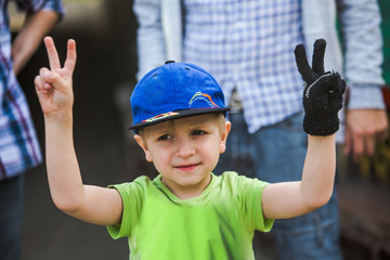 A child in a green T-shirt and blue blazer raised his two hands up. The child shows the victory sign with two fingers.