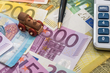 train above euro banknotes with pen and calculator