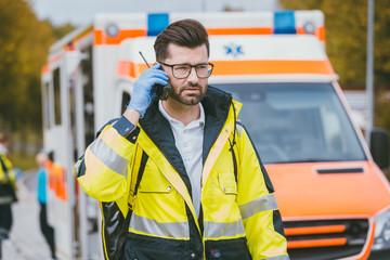Notarzt Mann spricht mit Einsatzleitung vor dem Krankenwagen