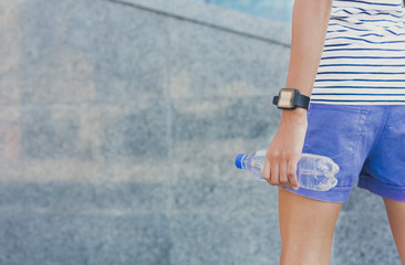 Girl holds bottle with water, crop