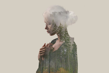 Double exposure. Creative. Beautiful girl with a forest and trees inside the body. Gray background