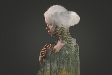 Beautiful woman with a forest, fog and city inside body on a dark background. Double exposure. Creative