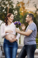 Man gives his pregnant wife flowers.