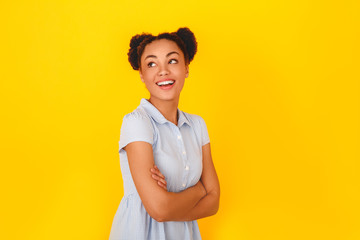 Young african woman isolated on yellow wall studio cute girl style dreaming