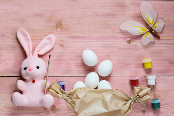 Easter festive set with eggs, flower and easter rabbit, paint, brush, wrapping paper on rustic wooden table with copyspace. Flat lay, space for mock up and copy space. Top view.