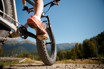 Image of girl in sneakers on bicycle against of mountains