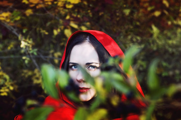 A girl in a red scarf with a piercing glance in the woods close up