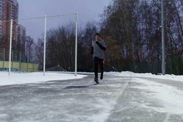 Image of athlete in black sports clothes running through winter