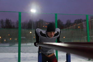 Image of sporty man pulling up on bar in evening at moon