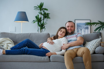 Picture of happy pregnant woman and man on gray sofa