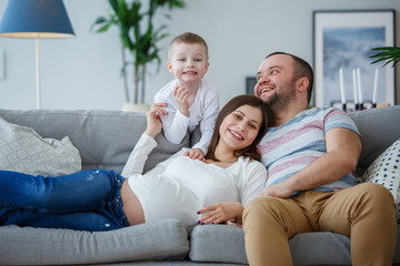 Photo of happy parents with small son on sofa