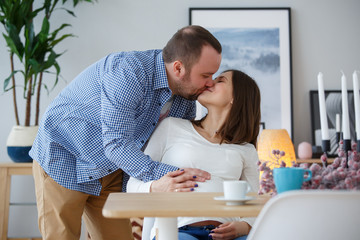 Image of happy husband kissing pregnant wife