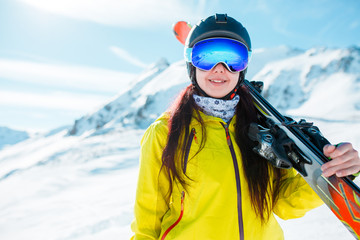 Picture of sports girl wearing helmet, mask with skis on her shoulder